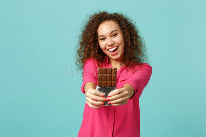 Portrait of happy pretty african girl in casual clothes hold in hand chocolate bar isolated on blue turquoise wall stock image