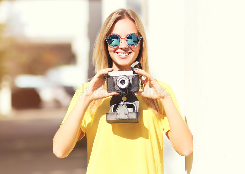 Portrait happy pretty blonde woman wearing sunglasses with camera royalty free stock photo
