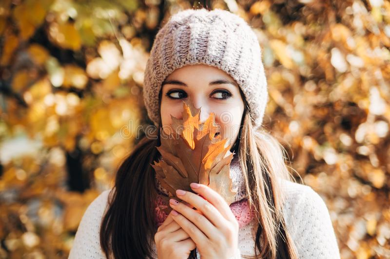 Portrait of happy pretty brunette girl,wearing knitted sweater and hat,in the autumn park.Bright sunny day.Good positive mood. Orange and yellow fallen leaves royalty free stock photos