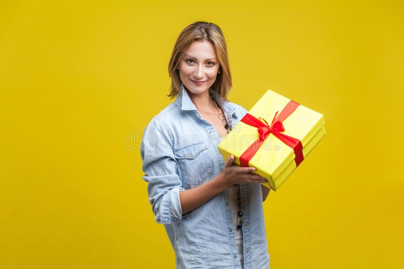 Portrait of happy pretty girl holding wrapped gift box and looking at camera with smile, enjoying holiday present. indoor studio royalty free stock photography