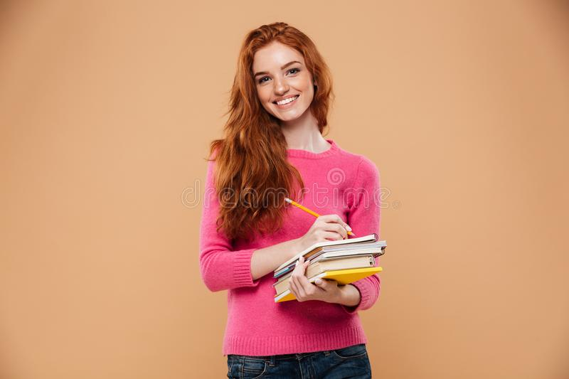 Portrait of a happy pretty redhead girl holding books royalty free stock image
