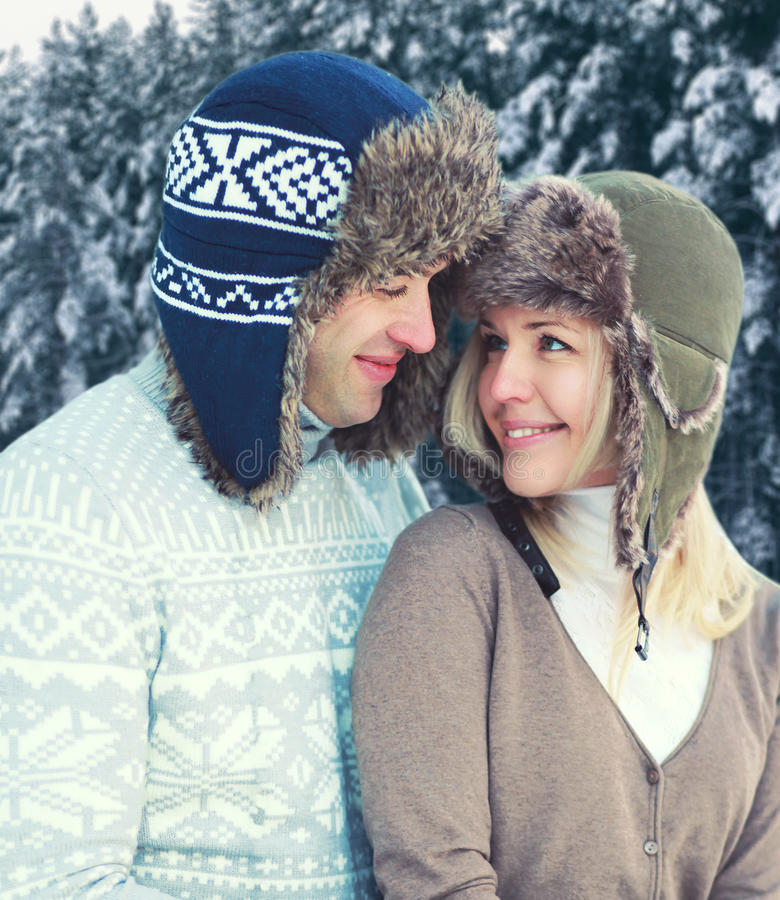 Portrait of happy pretty young smiling couple in warm winter day wearing hat and knitted sweater over snowy trees forest royalty free stock photo