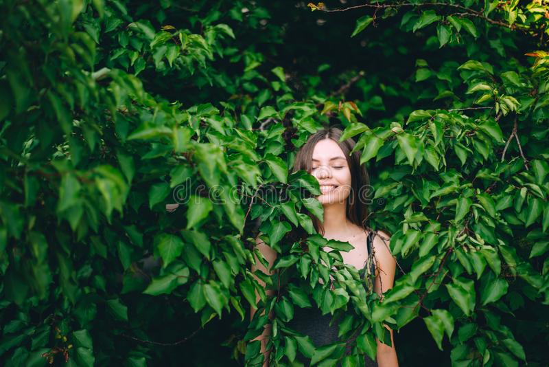 Portrait of happy pretty young teen girl in green leaves smiling healthy natural royalty free stock photography