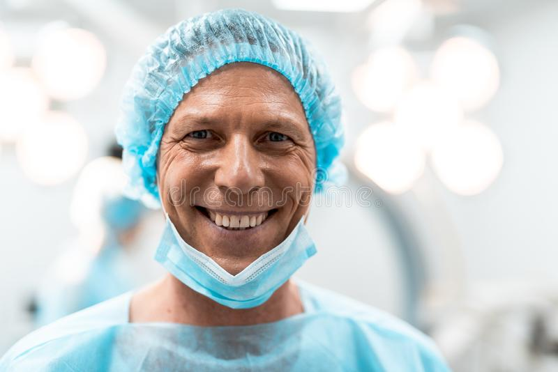 Close up of emotional doctor smiling happily after productive day stock images