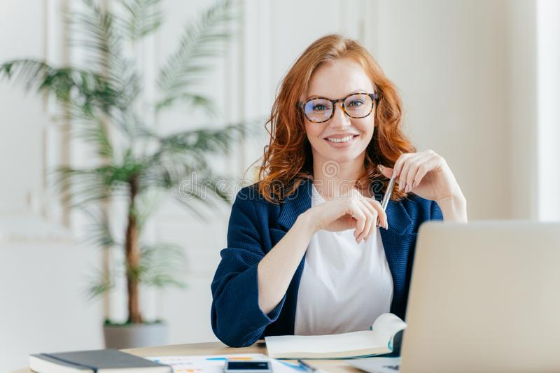 Portrait of happy redhaired woman employee in optical glasses, has satisfied expression, works with modern gadgets, waits for. Meeting with colleague, prepares royalty free stock images