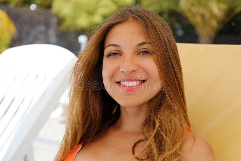 Portrait of happy relaxing woman sitting comfortable and looking at camera. Resting beautiful smiling girl enjoying her holidays. In Tenerife stock photo