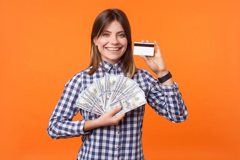 Portrait of happy rich brunette woman in checkered shirt holding dollars and bank card. indoor studio shot isolated on orange stock images