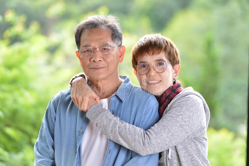 Portrait of happy romantic senior couple looking at the camera. On green nature background royalty free stock image