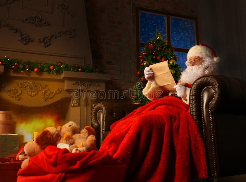 Portrait of happy Santa Claus sitting at his room at home near Christmas tree and reading Christmas letter or wish list. royalty free stock image