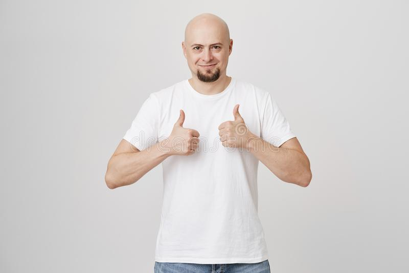 Portrait of happy satisfied bald bearded guy showing thumbs up and smiling, being pleased with item he bought, standing. Over gray background. Man gives stock photos