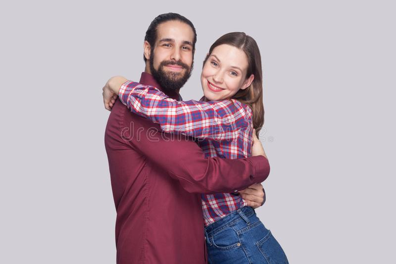 Portrait of happy satisfied bearded man and woman in casual style standing and hugging each other and looking at camera with toot royalty free stock photography