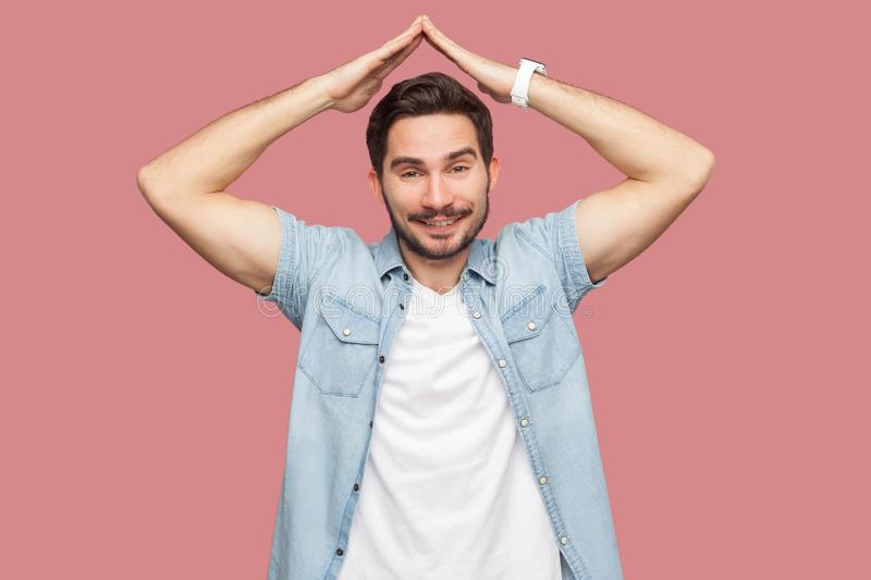Portrait of happy satisfied handsome bearded young man in blue casual shirt standing with roof gesture hands on head and looking stock photography