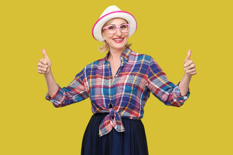 Portrait of happy satisfied modern stylish mature woman in casual style, hat and eyeglasses standing, thumbs up, looking at camera. With toothy smile. indoor royalty free stock photos