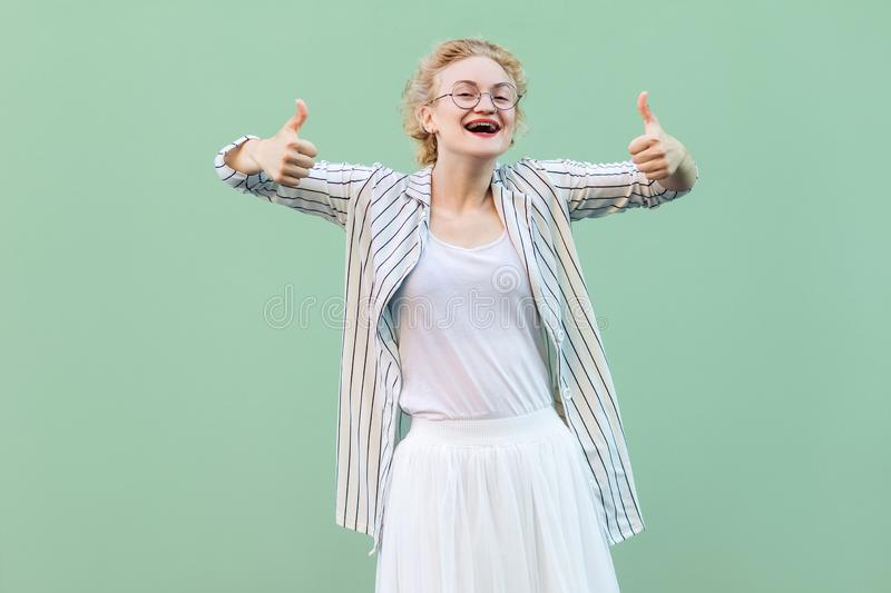 Portrait of happy satisfied young blonde woman in white shirt, skirt, striped blouse with eyeglasses standing, thumbs up and stock photos