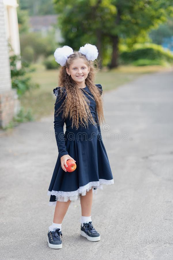 Portrait of a happy school girl standing with red apple on head. Farewell Bell. day of knowledge stock photography