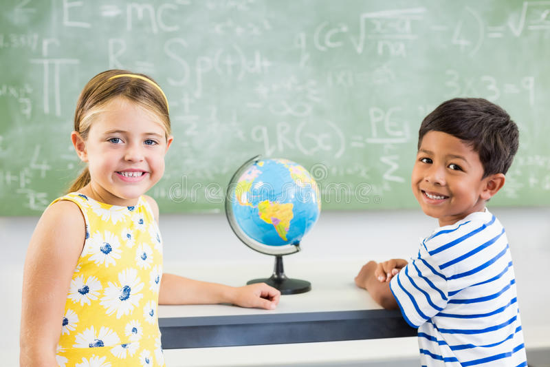 Portrait of happy school kids standing in classroom royalty free stock images
