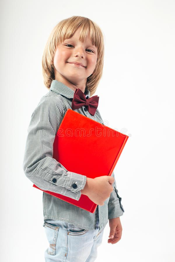 Portrait of happy schoolboy dressed in red bow tie with apple and red book isolated on white background. royalty free stock photography