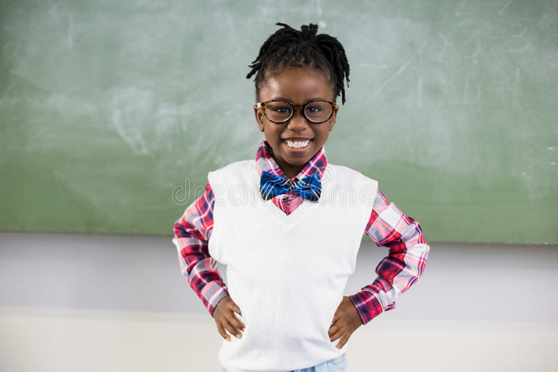 Portrait of happy schoolgirl standing with hand on hip royalty free stock photography