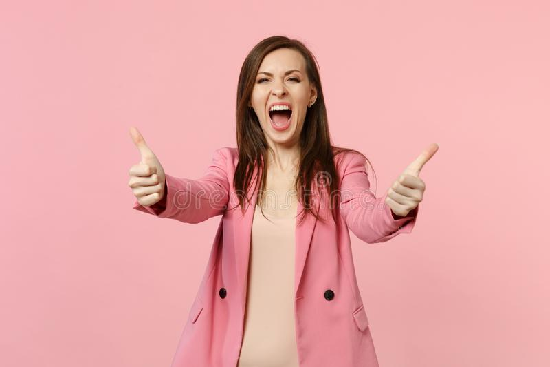 Portrait of happy screaming young woman wearing jacket looking camera showing thumbs up isolated on pastel pink wall royalty free stock photography
