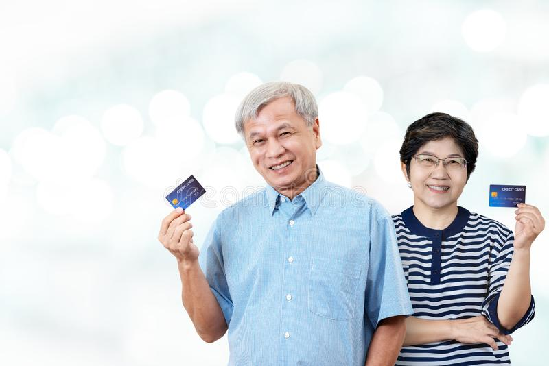 Portrait of happy senior asian parents holding credit card on hand smiling and looking at camera. On isolated blurred bokeh background feeling positive and royalty free stock photography