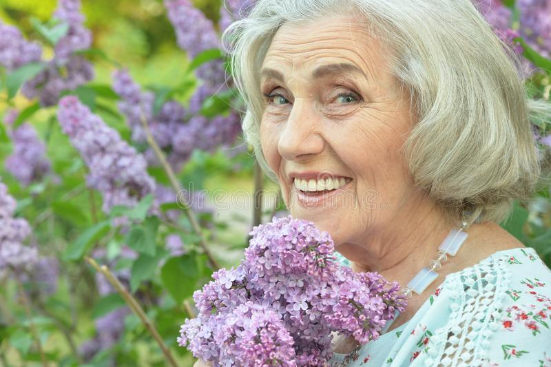 Portrait of happy senior beautiful woman with lilacs posing in spring park. Happy senior beautiful woman with lilacs posing in spring park royalty free stock photo