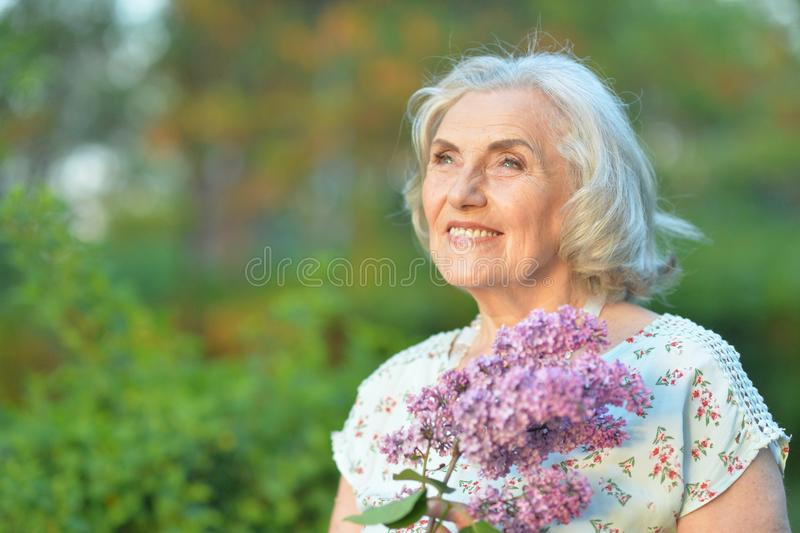 Portrait of happy senior beautiful woman with lilacs posing in spring park. Happy senior beautiful woman with lilacs posing in spring park royalty free stock photos