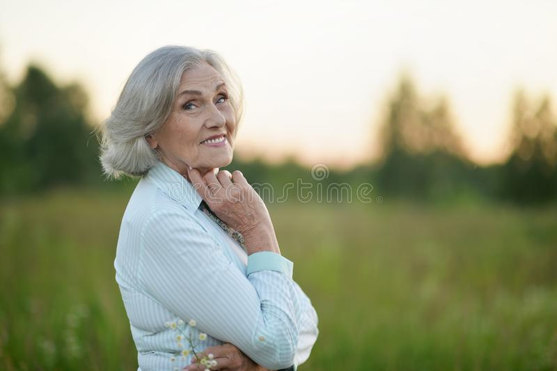 Portrait of happy senior beautiful woman posing in spring park. Happy senior beautiful woman posing in spring park stock photo