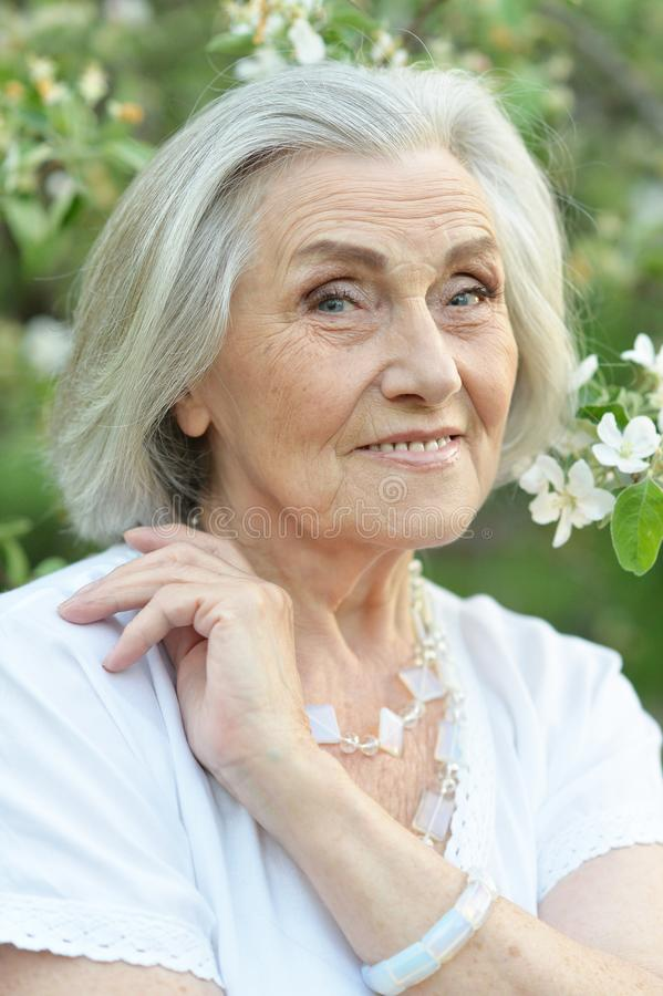 Portrait of happy senior beautiful woman in spring park. Happy senior beautiful woman in spring park with blooming apple tree background royalty free stock photos