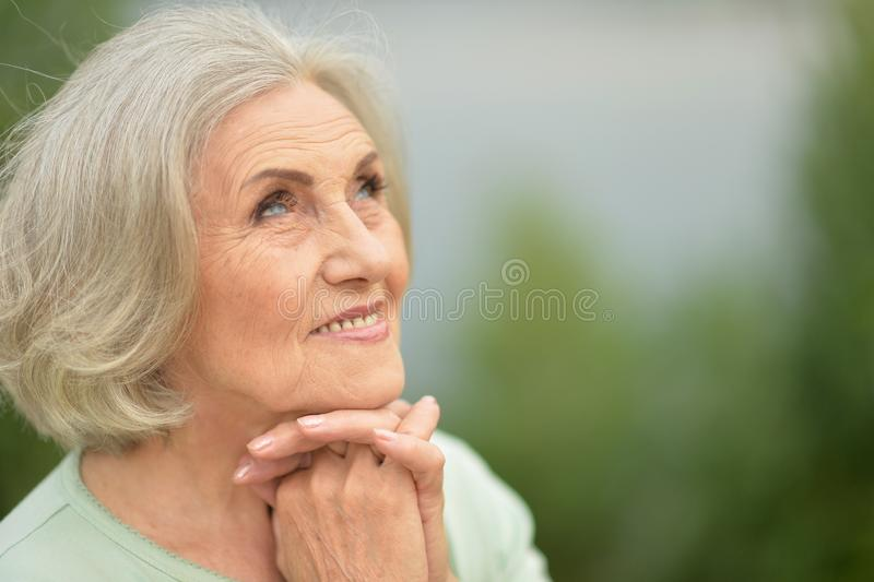 Portrait of happy senior beautiful woman in spring park. Happy senior beautiful woman posing in spring park royalty free stock photos