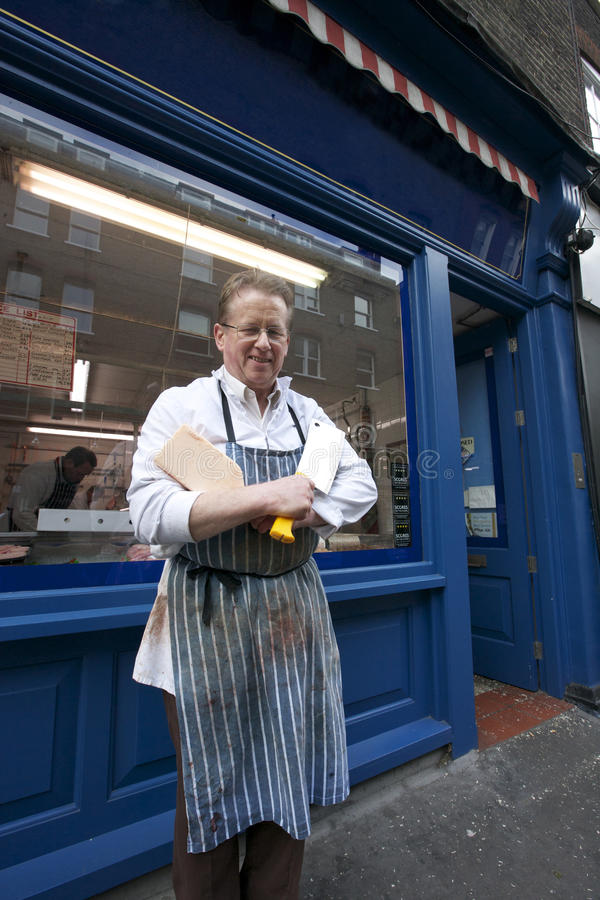 Portrait of a happy senior butcher standing outside shop with cleaver stock photo