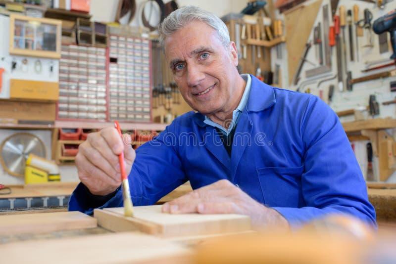 Portrait happy senior carpenter varnishing wood in workshop royalty free stock image