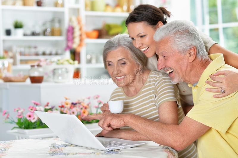 Portrait of happy senior couple with adult daughter using laptop at home, online shopping concept royalty free stock photos