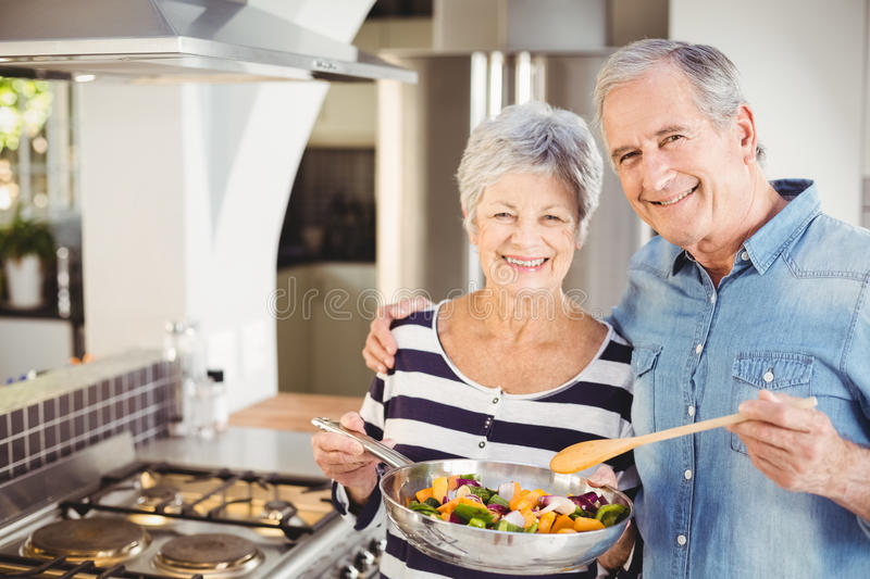 Portrait of happy senior couple with cooking pan stock photography