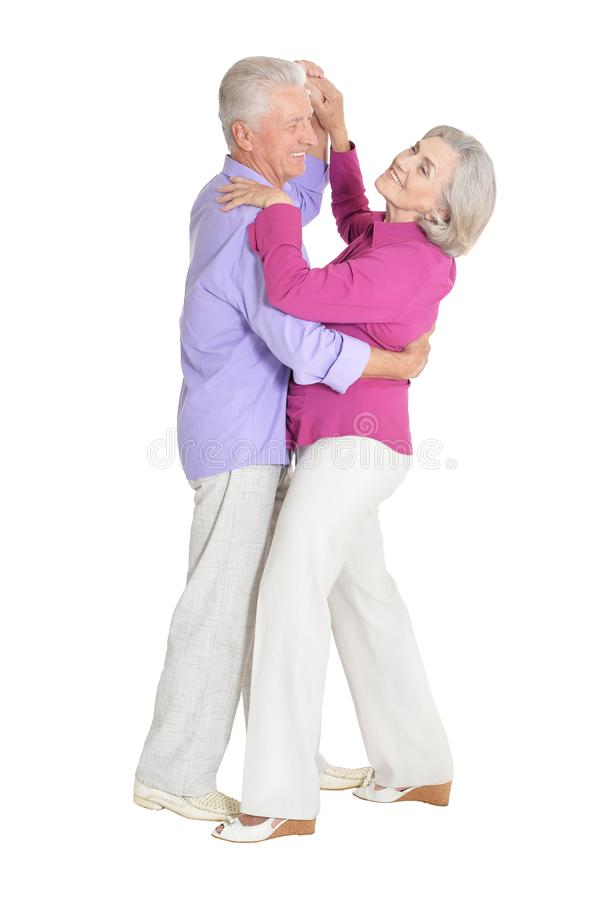 Portrait of happy senior couple dancing on white background stock photography