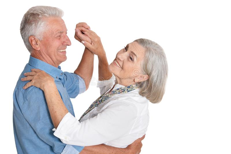 Portrait of happy senior couple dancing on white background stock images