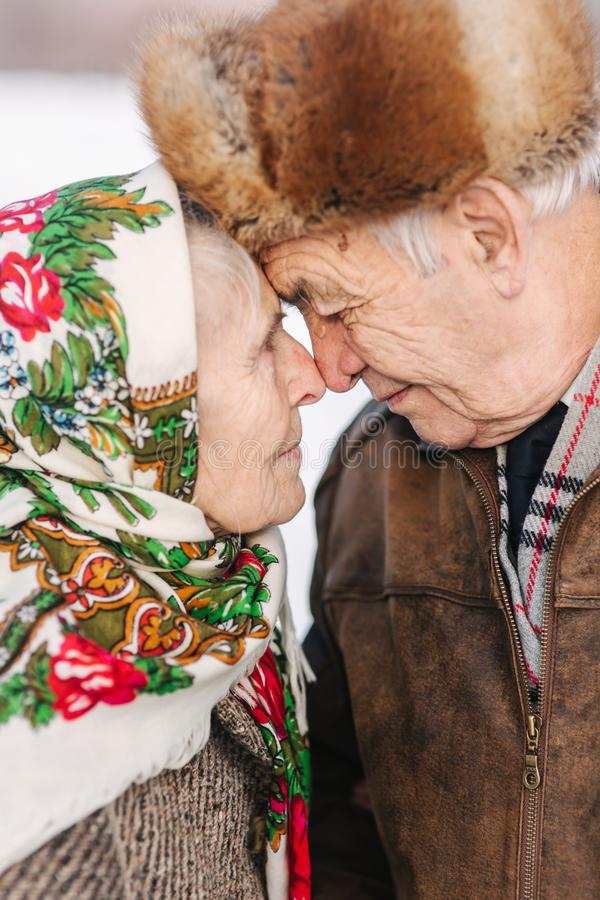 Portrait of happy senior couple. Elderly woman kiss her husband in weighty. old couple walking in the park in winter. Portrait of happy senior couple. Elderly royalty free stock photography