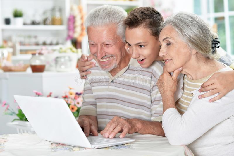 Portrait of happy senior couple with grandson using laptop at home stock photos