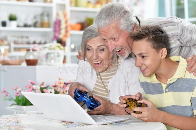 Portrait of happy senior couple with grandson using laptop playing game stock photography