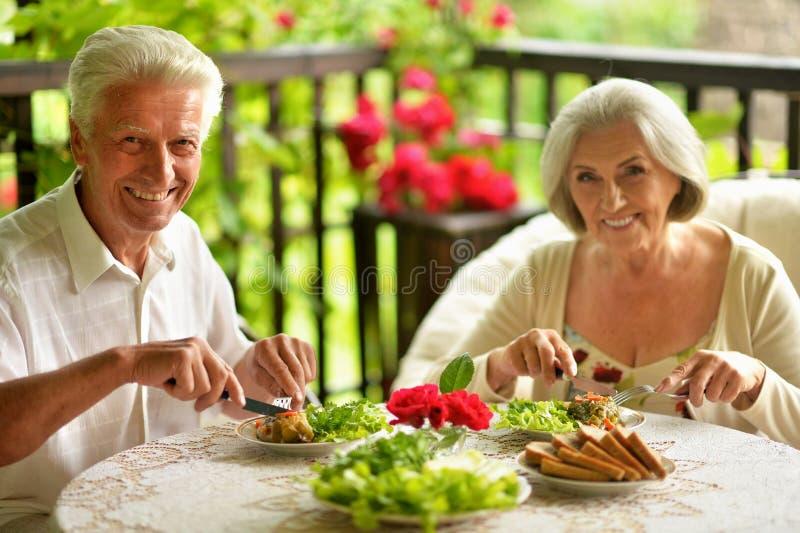 Portrait of happy senior couple having diner stock photos