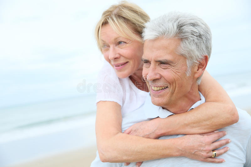 Portrait of happy senior couple having fun on the beach stock photo