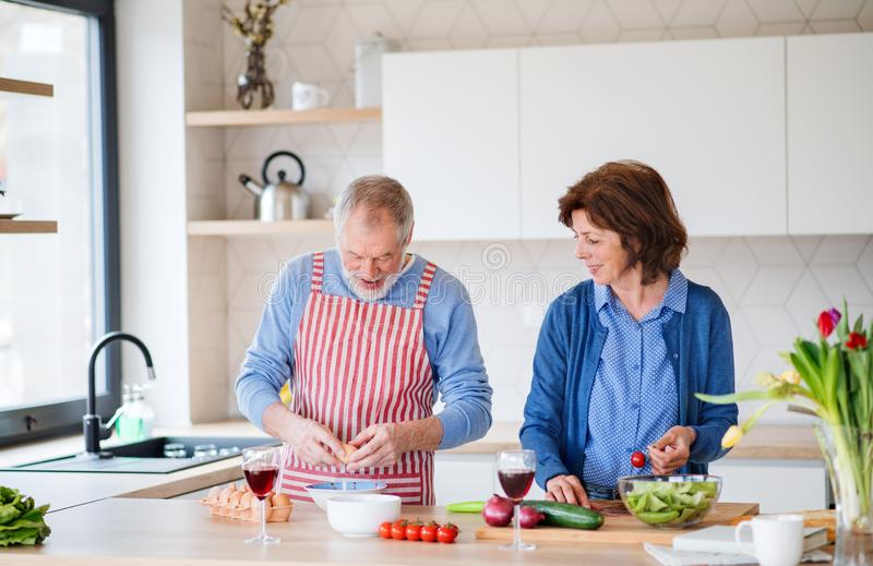 A portrait of senior couple indoors at home, cooking. A portrait of happy senior couple indoors at home, cooking stock images