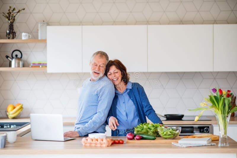 A portrait of senior couple with laptop indoors at home, cooking. A portrait of happy senior couple with laptop indoors at home, cooking royalty free stock image
