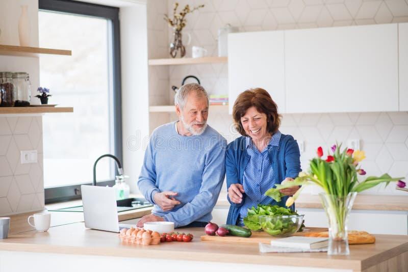 A portrait of senior couple with laptop indoors at home, cooking. A portrait of happy senior couple with laptop indoors at home, cooking royalty free stock photo