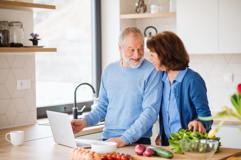 A portrait of senior couple with laptop indoors at home, cooking. A portrait of happy senior couple with laptop indoors at home, cooking royalty free stock images