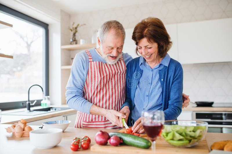 A portrait of senior couple in love indoors at home, cooking. A portrait of happy senior couple in love indoors at home, cooking stock photography