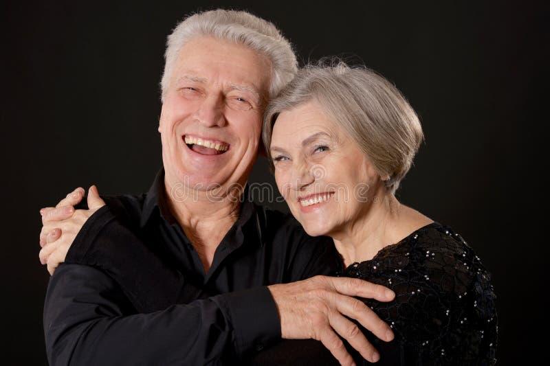 Portrait of happy senior couple posing on black background stock image