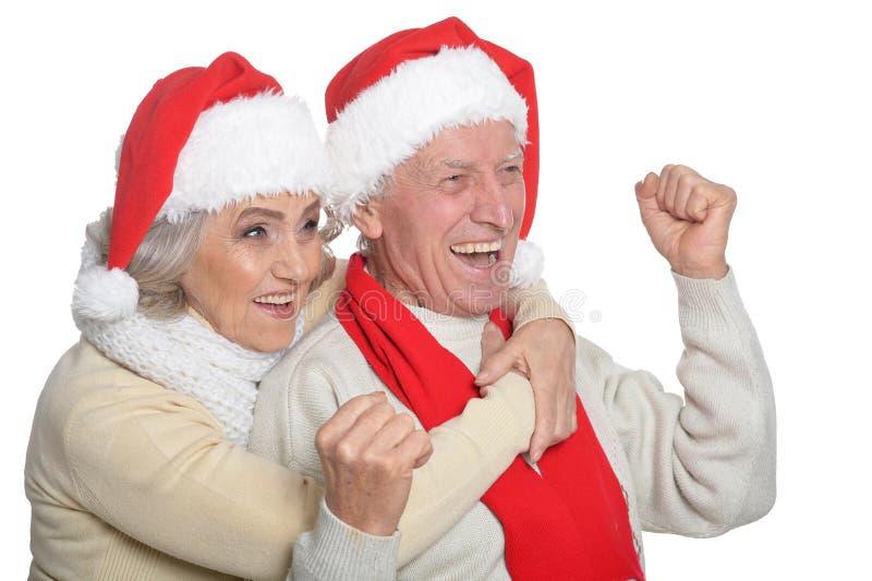 Portrait of happy senior couple in Santa hats stock images