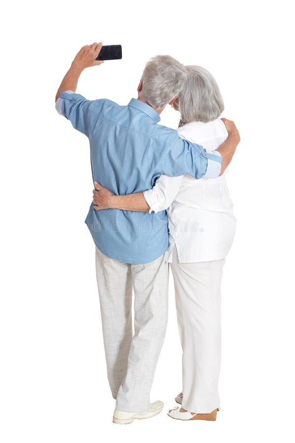 Portrait of happy senior couple taking selfie on white background stock photo