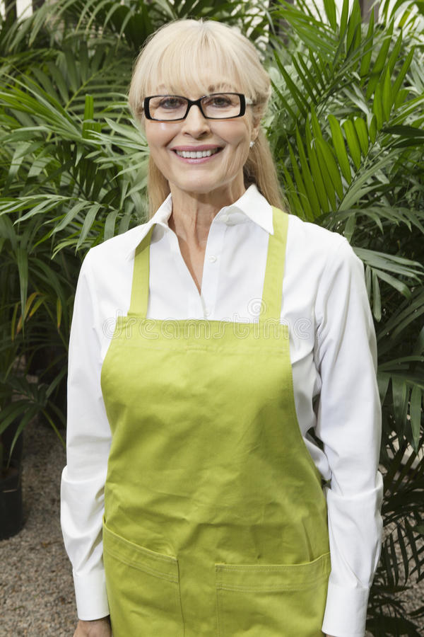 Portrait of a happy senior female gardener with apron standing in botanical garden stock image