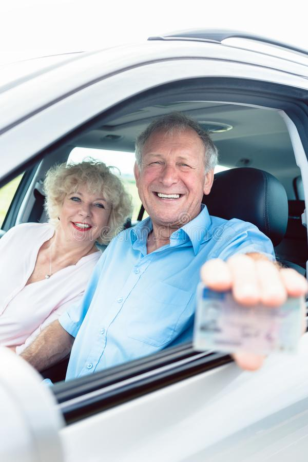 Portrait of a happy senior man showing his driving license. Portrait of a happy senior men showing his available driving license while sitting in the car next to stock photography